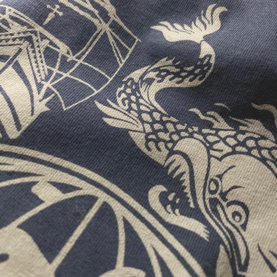 Detalle de una sección del estampado de la camiseta homenaje a Elcano, en que se muestra a una criatura marina junto a la Nao Victoria.