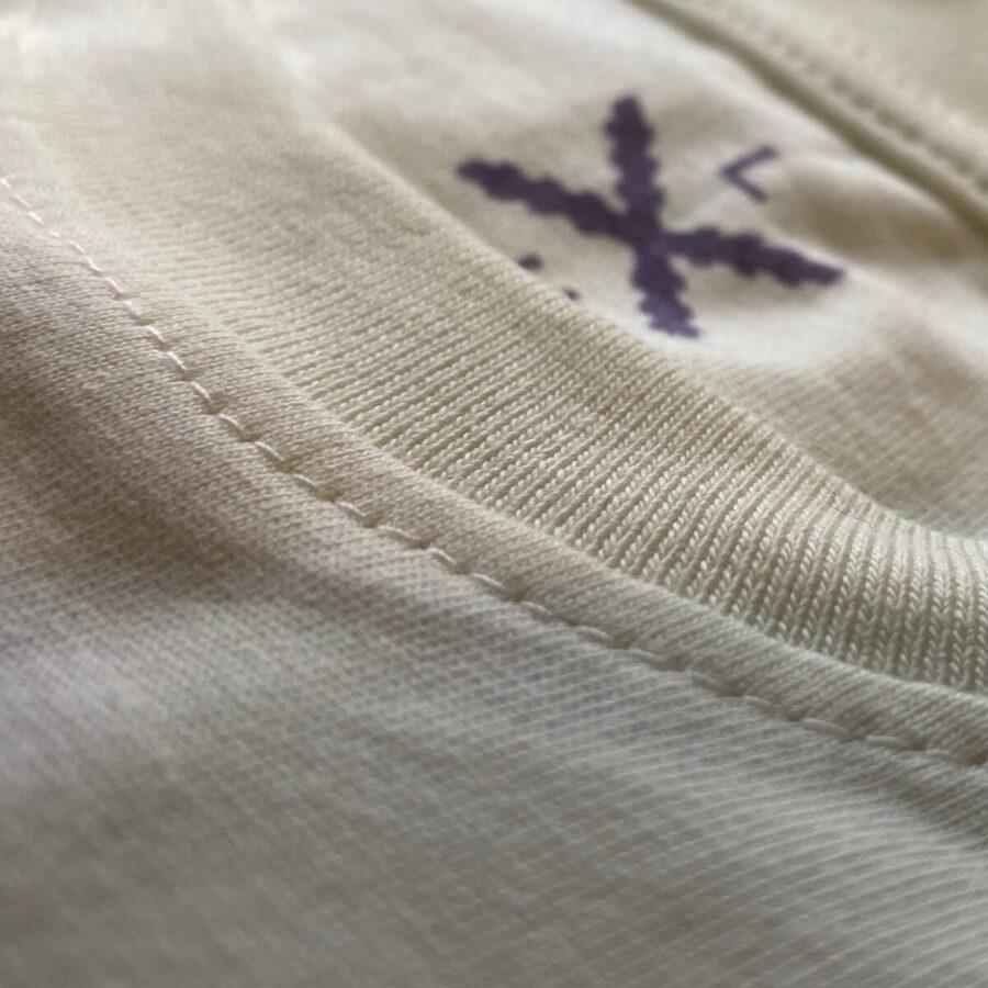 Detalle de la costura del cuello de camiseta en color blanco, con el logo asomando desde el interior.